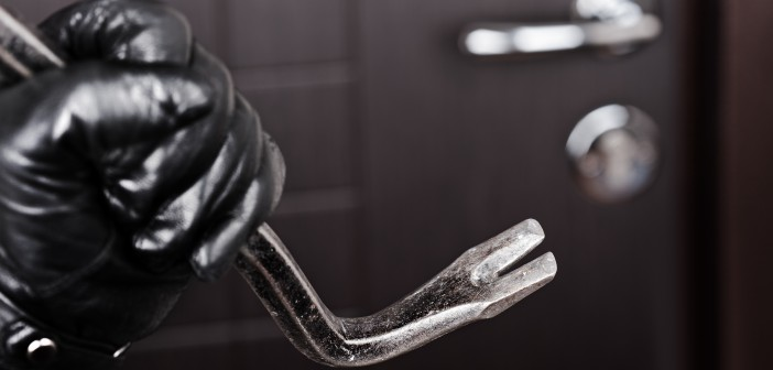 Burglar hand holding crowbar break opening door